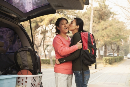 college student: Mother and daughter embracing behind car on college campus Stock Photo