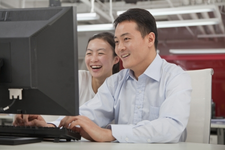 chinese women: Happy business people working on their computer in the office