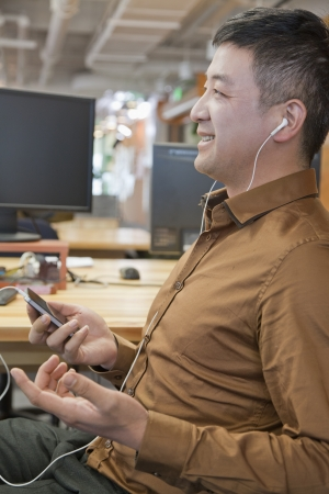 portable mp3 player: Businessman Listening Music in the Office