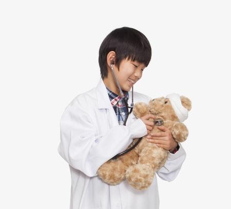 signos vitales: Niño vestido como los signos vitales del médico de control de oso de peluche