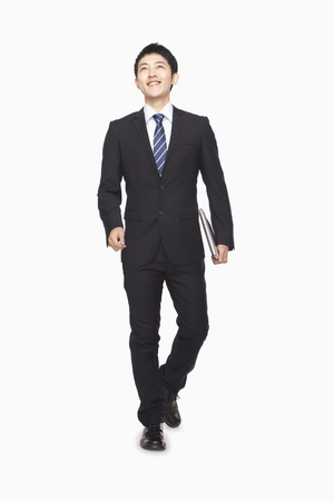 chinese people: Businessman walking while carrying laptop