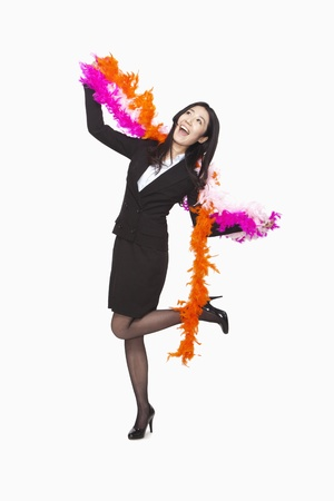 feather boa: Businesswoman dancing with feather boa Stock Photo