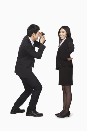 Businessman photographing businesswoman photo