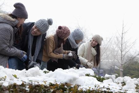 雪の中で遊んでいる友人のグループ