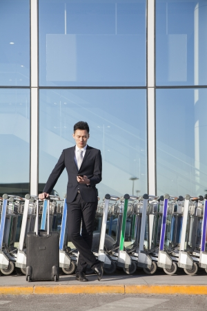 Traveler looking at cellphone next to row of luggage carts photo
