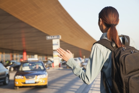 incidental people: Young traveler hailing a taxi at airport