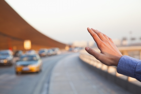 hailing: Hand of traveler hailing a taxi outside of the airport