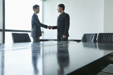 business: Businessmen shaking hands in meeting room Stock Photo