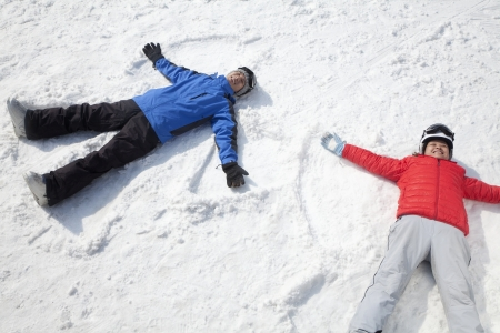 雪の天使を作る雪の上に横たわるカップル