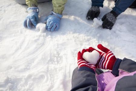 雪で遊ぶ冬の手袋での手のクローズ アップ