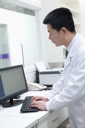 one mid adult man: Male veterinarian using computer