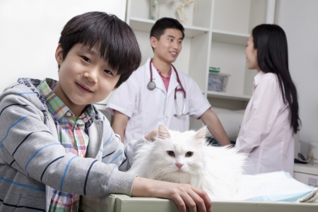 Boy with pet dog in veterinarians office photo