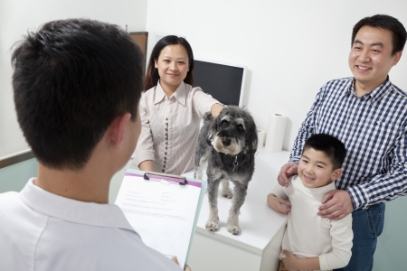 pampered pets: Family with pet dog in veterinarians office