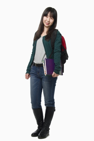high school series: Smiling female student carrying books, portrait