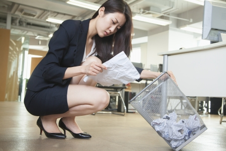 Young businesswoman reading piece of paper from the trash can in office