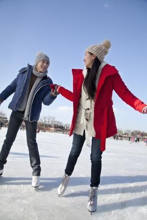 Young couple skating at ice rink photo