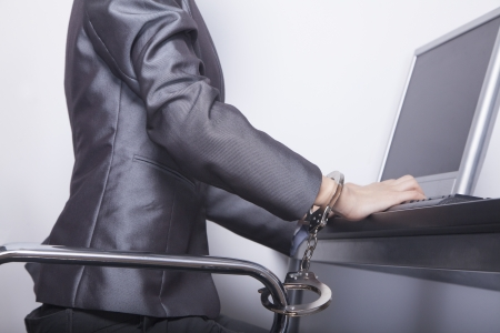 Young businesswoman handcuffed to her office chair photo