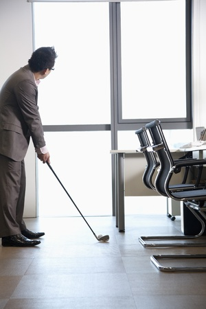 wasting away: Businessman playing golf in his office Stock Photo
