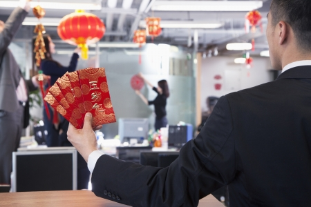 Businessman holding red envelopes and coworkers hanging decorations for Chinese new year