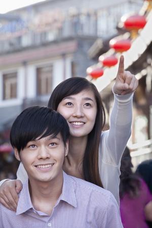 Young Heterosexual Couple Pointing Outdoors in Beijing Stock Photo