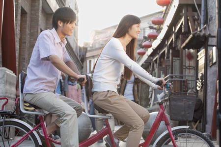 tandem bicycle: Side View of Young Heterosexual Couple on a Tandem Bicycle in Beijing  Stock Photo
