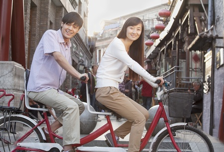 Side View of Young Heterosexual Couple on a Tandem Bicycle in Beijing Looking at Camera Stock Photo