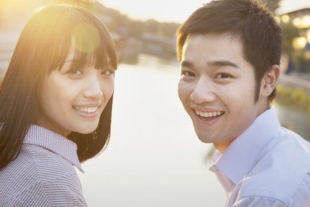 Happy Young Couple Looking at the Camera by a River