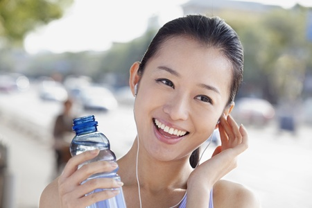 bottled water: Young Woman with Bottled Water Listening to Music