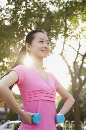flare up: Young Woman Exercising in Park with Dumbells Stock Photo
