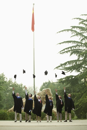 medium length: Young Group of University Graduates Throwing Mortarboards in the Air, Vertical