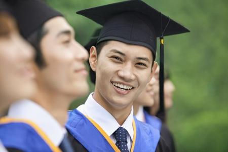 birrete de graduacion: El hombre joven sonriente en una fila de j�venes titulados universitarios