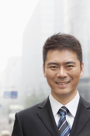 looking into camera: Young Businessman Smiling and Looking into Camera, Portrait