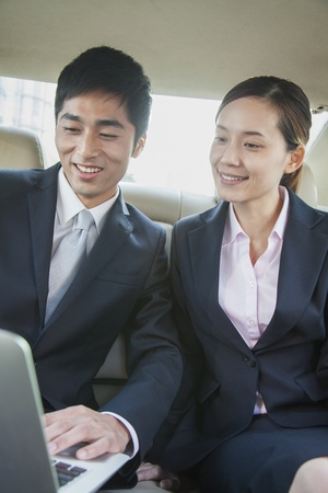 Business Colleagues Using Laptop in Back Seat Of Car Imagens