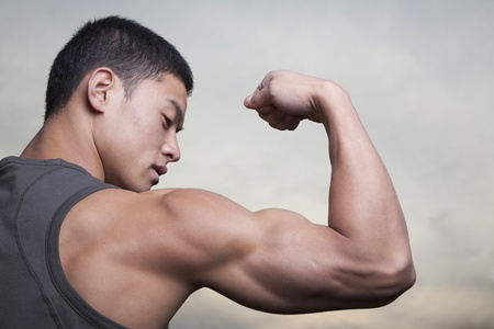 bicep: Young Man showing off his bicep muscles