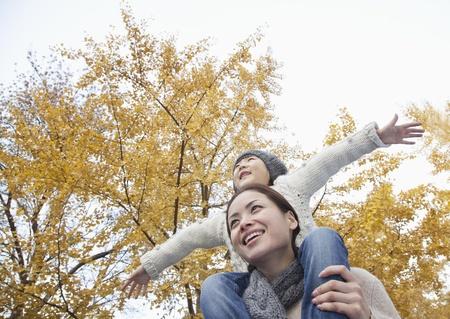 madre soltera: Madre e hija con los brazos extendidos y rodeado de �rboles de oto�o