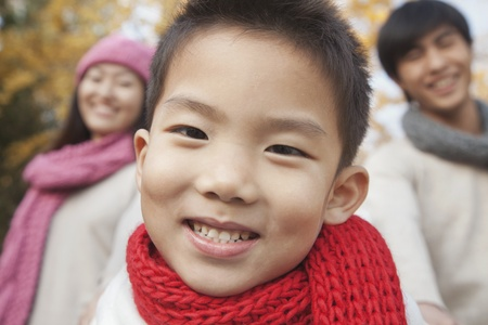 Close Up of Young Boy with Family in Park in Autumn photo