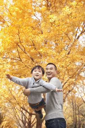 recreational area: Father and Son Playing at Park in Autumn