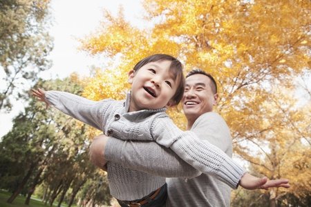 Father and Son Playing at Park in Autumn photo