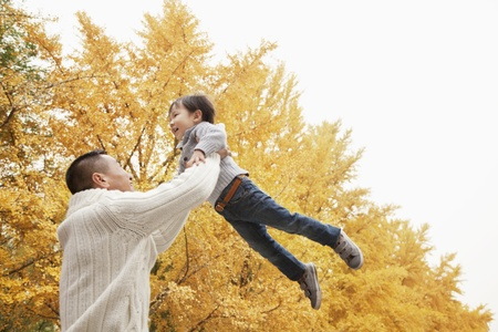 autumn hair: Father And Son Playing a Park in Autumn Stock Photo