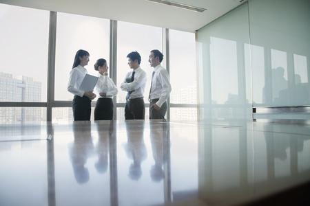 personas de pie: Cuatro j�venes de negocios de pie junto a la mesa de conferencias