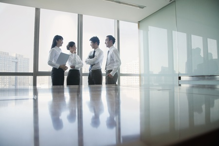 city people: Four Young business people standing by conference table