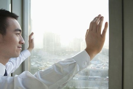Young Businessman Looking out the window in Beijing photo