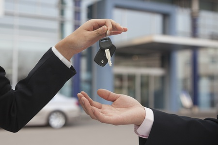 key to freedom: Salesman handing over car keys, close up on hands