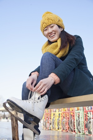 incidental people: Young Woman Tying Ice Skates Outside
