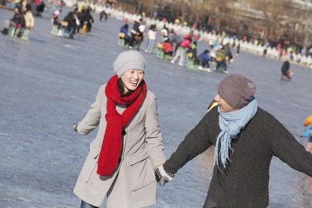 skating: Young Couple Ice Skating, Sitting on Ice Sled