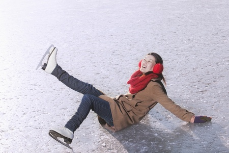 ice skate: Young Woman Falling While Ice Skating Stock Photo