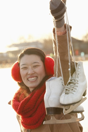 Young Woman Holding Up Ice Skates Outside, Beijing photo