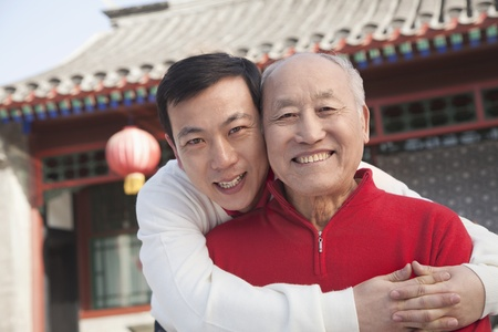 adult offspring: Portrait of father and son outside traditional Chinese building