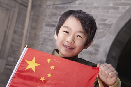 Young Boy in Traditional Courtyard with Chinese Flag Stock Photo