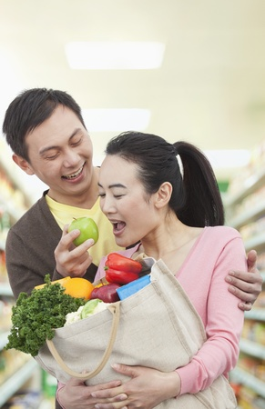 Man Feeding Woman Apple in Grocery Store photo